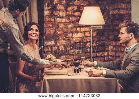 Waiter serving a plate of salad to a beautiful woman guest in a restaurant.