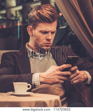 Stylish wealthy man using mobile phone in a restaurant.