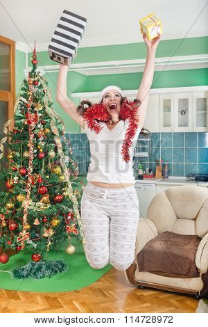 Excited Young Woman Jumping Of Joy With Gifts In Hands