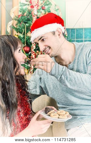 Man Feeding Woman With Sweet Cookies Or Cake From A Plate