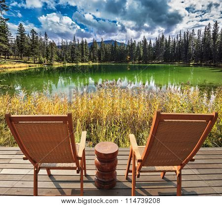 Autumn day in Jasper  National Park in the Rocky Mountains of Canada. Two wooden deckchairs for tourists on the shore of shallow circular lake