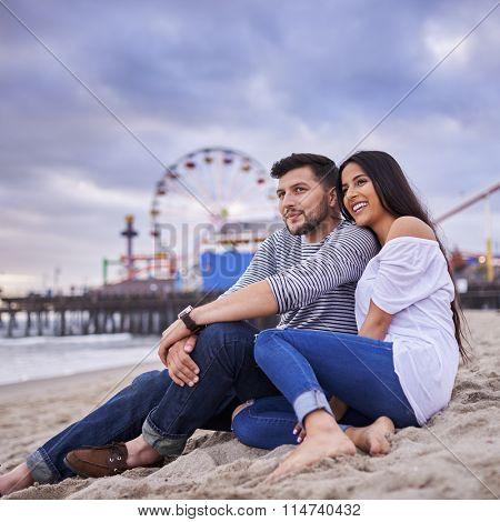romantic Hispanic couple cuddling on beach at Santa Monica California shot with selective focus