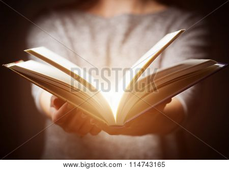 Light coming from book in woman's hands in gesture of giving, offering. Concept of wisdom, religion, reading, imagination.