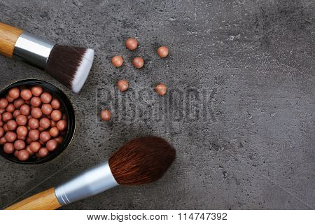 Assortment of make-up brushes and blusher, on grey background