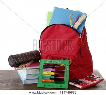 Backpack with school supplies on wooden table   with white background