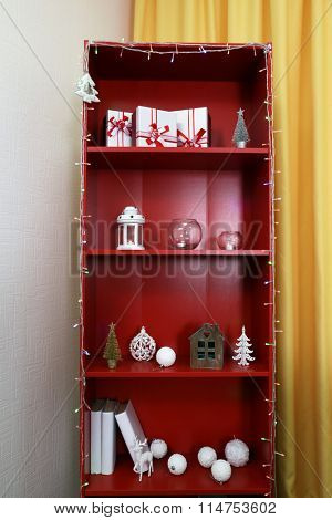 Red bookcase with white accessories, close up