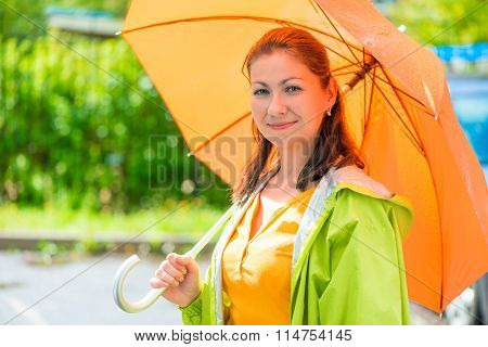 Portrait Of A Beautiful Girl With An Orange Umbrella Closeup