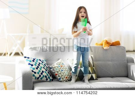 Beautiful little girl singing in a green hairbrush on sofa in the room