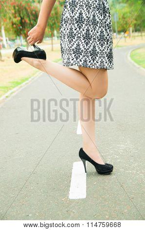 Classy woman wearing fashionable skirt and elegant black high heels bending right knee lifting shoe