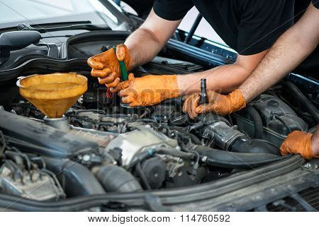 Two Mechanics Working On A Vehicle