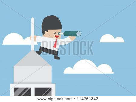 Businessman Looking Through Spyglass On The Top Of Building