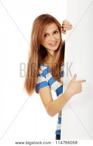 Smiling teenage woman pointing for empty banner