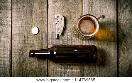 Beer Set: Bottle , Glass Of Beer, Bottle Opener, Cork On Wooden Background.