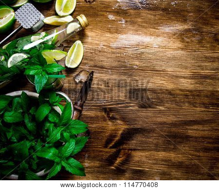 The Ingredients For The Cocktail - Limes, Rum, Mint Leaves, Ice Cubes On Wooden Table. Free Space Fo