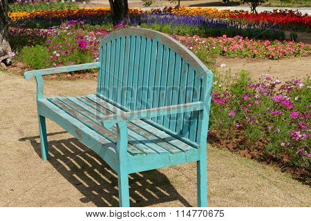 Green Bench And Blooming Flower At The Flowerbed