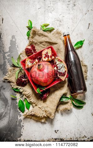 Pomegranate Juice In A Bottle And Pieces Of Pomegranates With Leaves On An Old Fabric .
