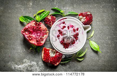 Juicer With Bits Of Pomegranates And Leaves. On Stone Table.