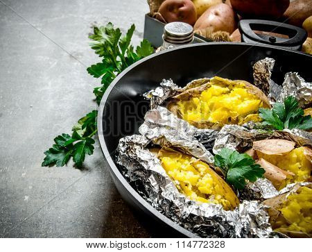 Baked Potatoes In A Pan On An Old Rustic Table .