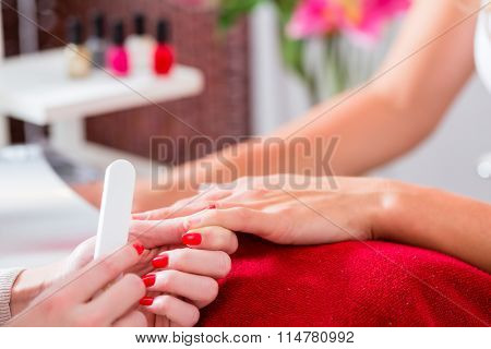 Woman getting manicure in nail parlor with file, close shot