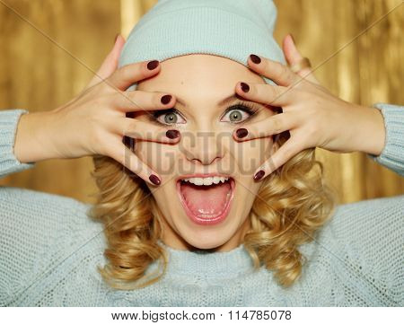 Surprised or shocked attractive young blond woman with ringlets and huge blue eyes holding her hands with manicured red nails over her mouth in a close up head shot