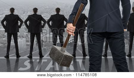 Startup concept. Determined businessman with hammer in hands