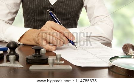 Woman notary, lawyer signs the documents in office