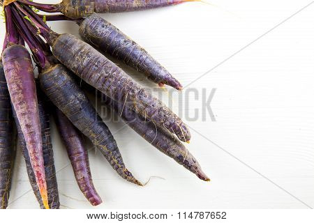 Bunch Of Heirloom Purple Carrots, Over White And Wooden Background