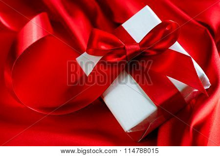 Valentine Gift box with red satin ribbon on Red Silk Background over glowing holiday background. Romantic St. Valentine's Day card design. Love