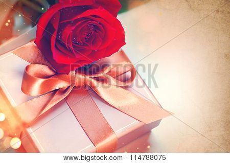 Rose and Gift box. Valentine's Day Red Rose and gift with silk bow over vintage background. Wedding or Valentines Gift. Art design with bunch of beautiful flowers and red satin ribbon closeup