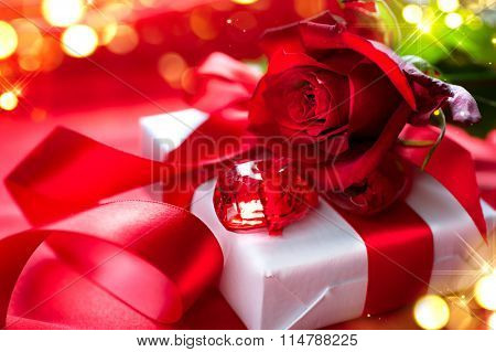 Roses and Gift box. Valentine's Day Red Rose and gift over silk background. Wedding or Valentines Gift. Art design with bunch of beautiful flowers and red satin ribbon closeup