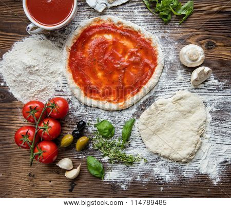Pizza dough on rustic wooden table