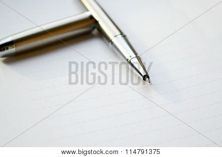 Empty sheet of white paper with a pen