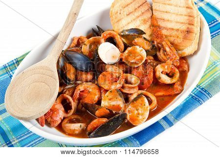fresh seafood soup with baked bread on dish