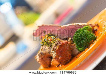 Delicious medium rare sirloin steaks and vegetables placed on orange plate, elegant presentation