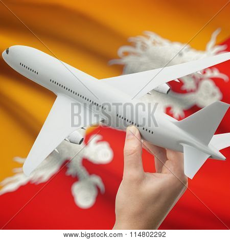 Airplane In Hand With Flag On Background - Bhutan