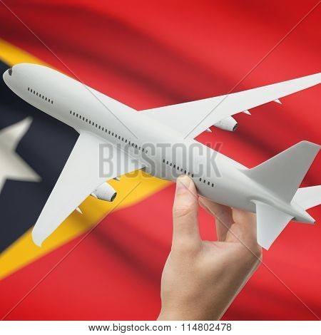 Airplane In Hand With Flag On Background - East Timor