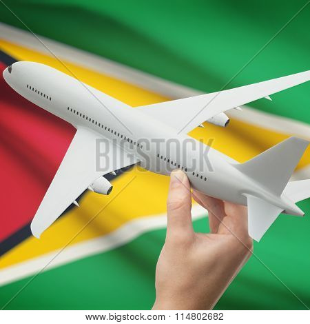 Airplane In Hand With Flag On Background - Guyana