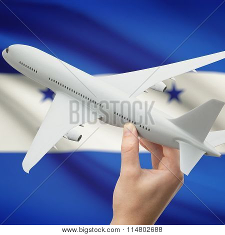 Airplane In Hand With Flag On Background - Honduras