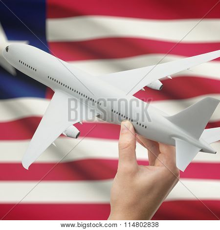 Airplane In Hand With Flag On Background - Liberia