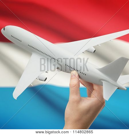 Airplane In Hand With Flag On Background - Luxembourg
