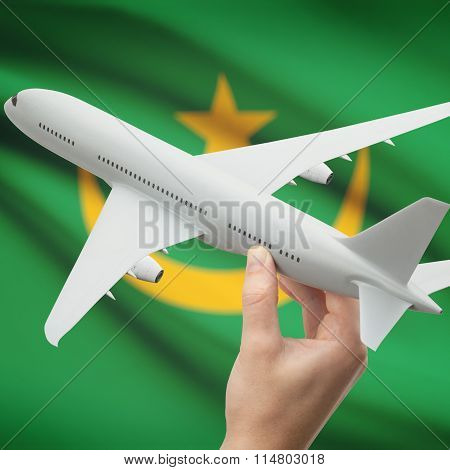 Airplane In Hand With Flag On Background - Mauritania