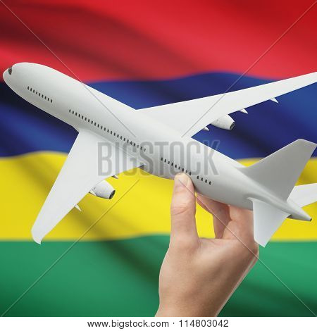 Airplane In Hand With Flag On Background - Mauritius