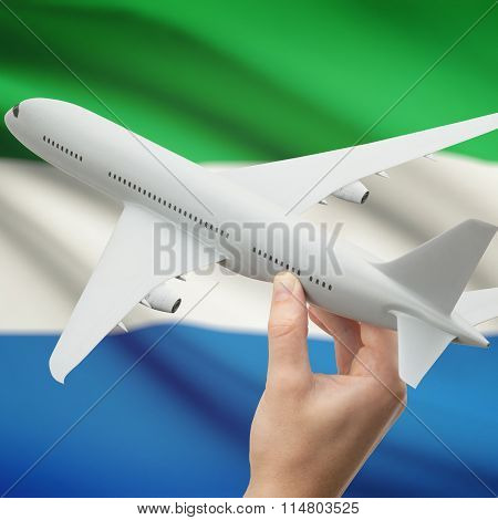 Airplane In Hand With Flag On Background - Sierra Leone