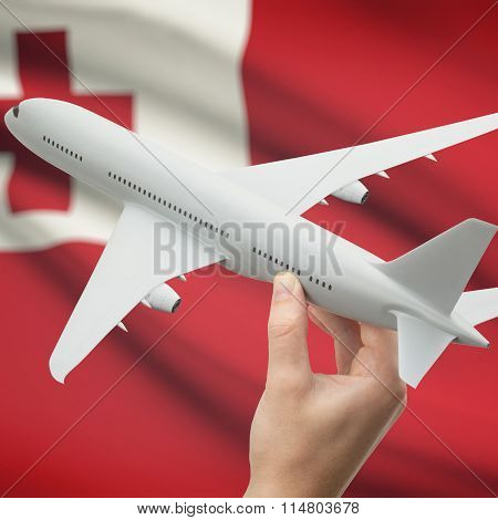 Airplane In Hand With Flag On Background - Tonga