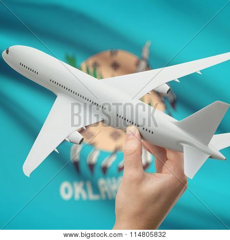 Airplane In Hand With Us State Flag On Background - Oklahoma