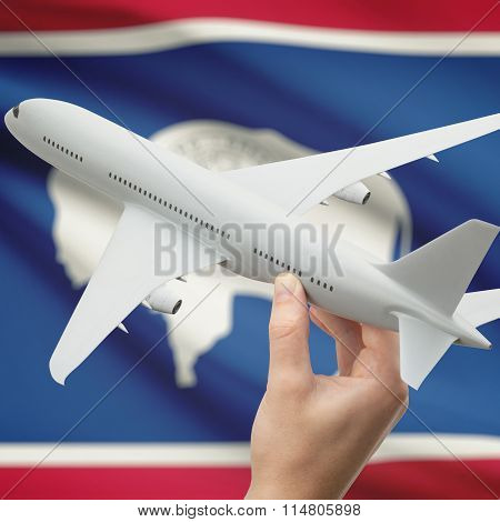 Airplane In Hand With Us State Flag On Background - Wyoming