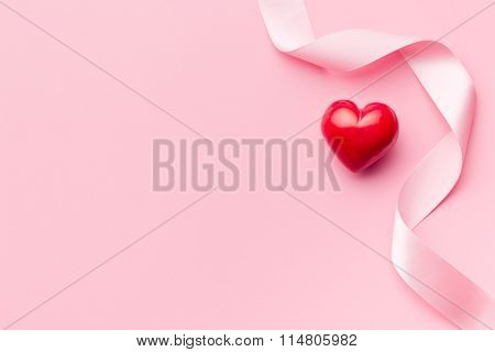 pink ribbon with red heart on pink background