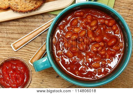 Bowl of Baked Beans and Ketchup at Table top view.
