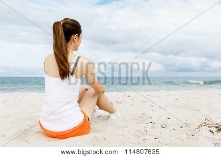 Young woman in sports wear sitting at the beach