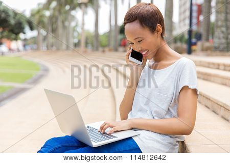 happy young african girl talking on mobile phone and using laptop